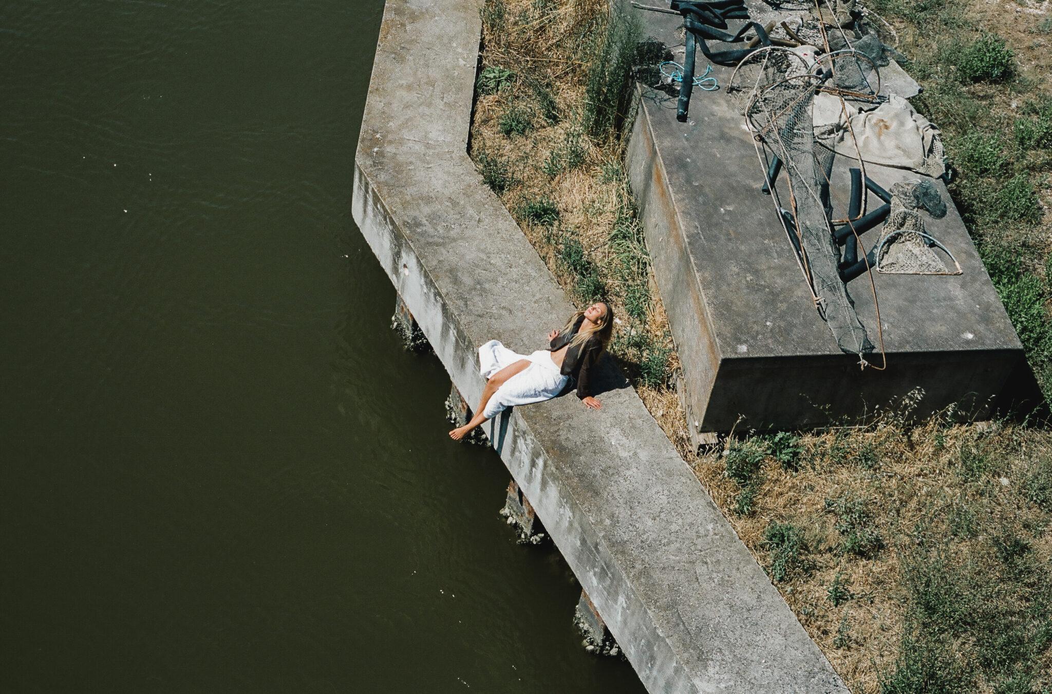 Fotografia aerea di mdella con gonna a portafoglio bianca, giacca di pelle marrone, prende il sole seduta su un argine palustre, fotografia analogica