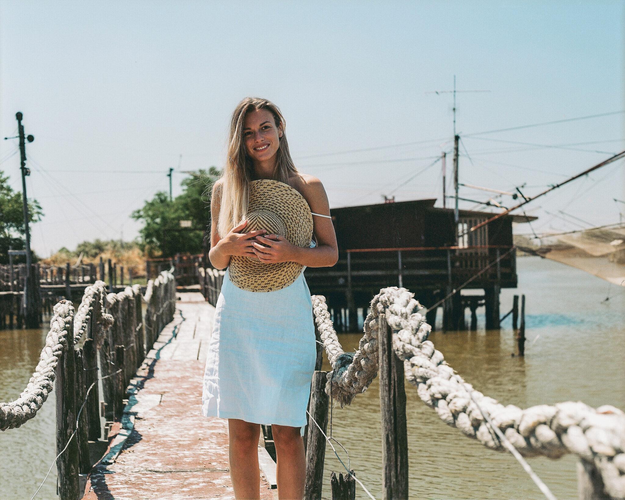 Modella con vestito azzurro e cappello di paglia, su un ponte in mezzo a una palude, fotografia analogica medio formato