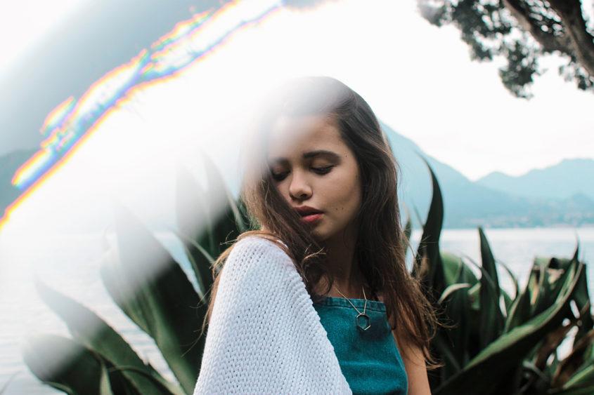 Modella con top di jeans, collana geometrica e agave e il lago sullo sfondo, con giochi di luce