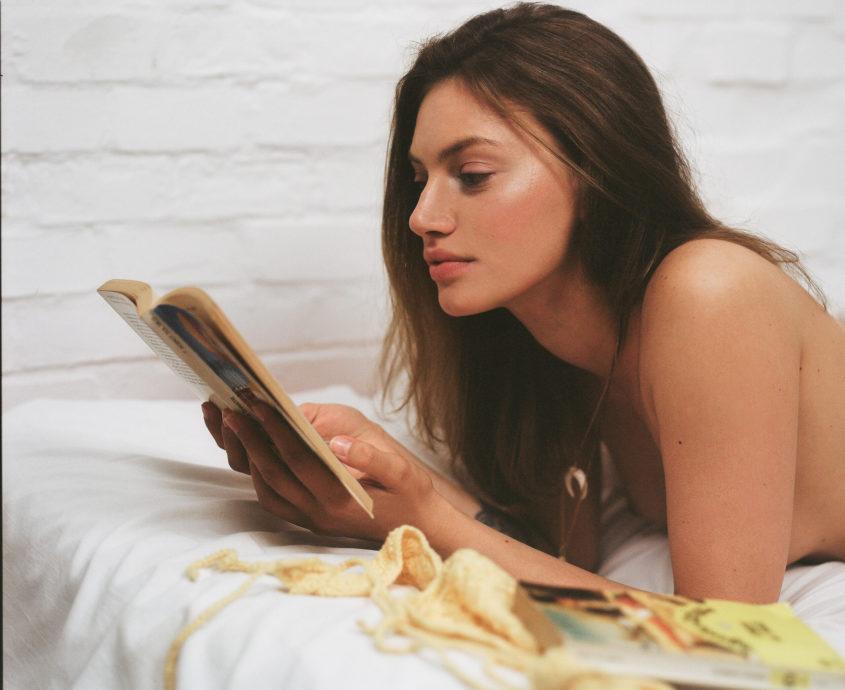 Modella sdraiata legge un libro, fotografia analogica con Mamiya RZ67 medio formato