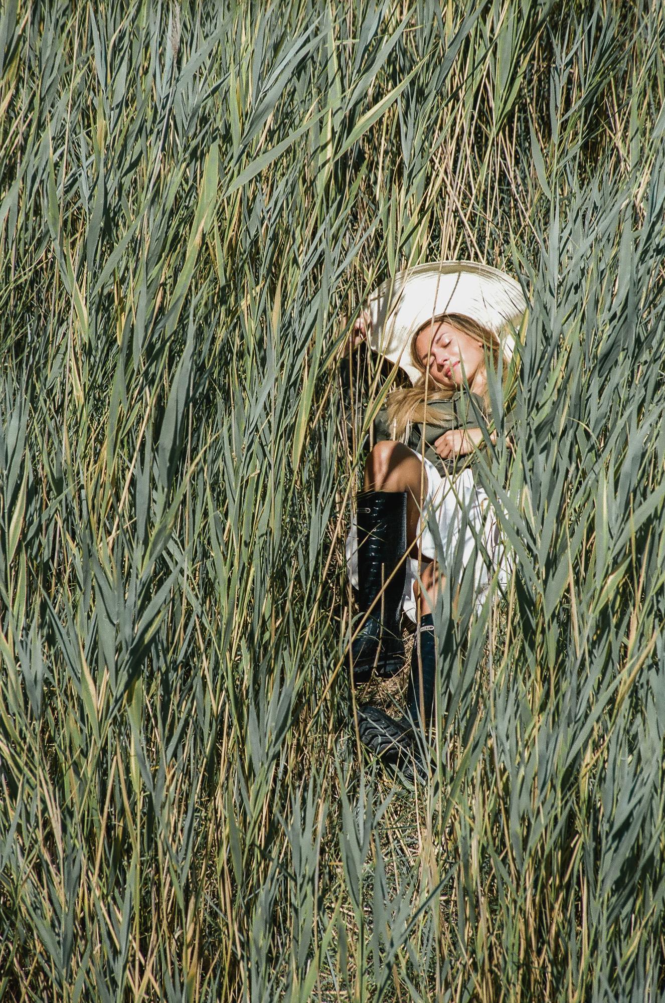 Fotografia di modella con cappello di paglia e stivali che riposa in mezzo a un campo di grano verde, fotografia analogica