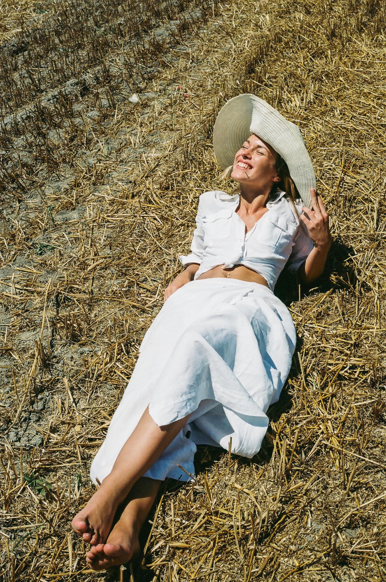 Modella che ride con camicia bianca annodata, gonna bianca e capello di paglia, sdraiata in mezzo a un campo di grano, con spiga tra i denti, fotografia analogica