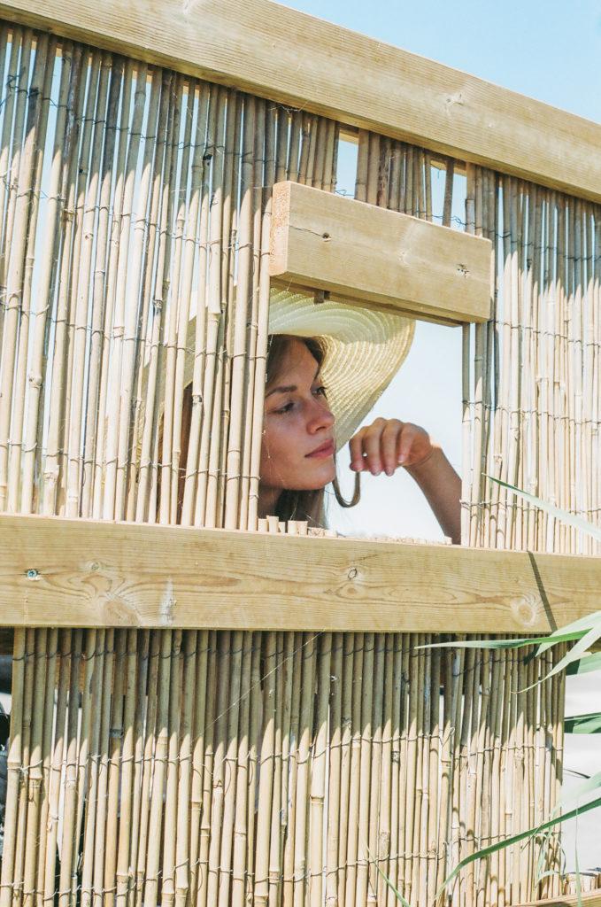 Modella con cappello di paglia guarda attraverso un punto di osservazione della fauna palustre, fotografia analogica