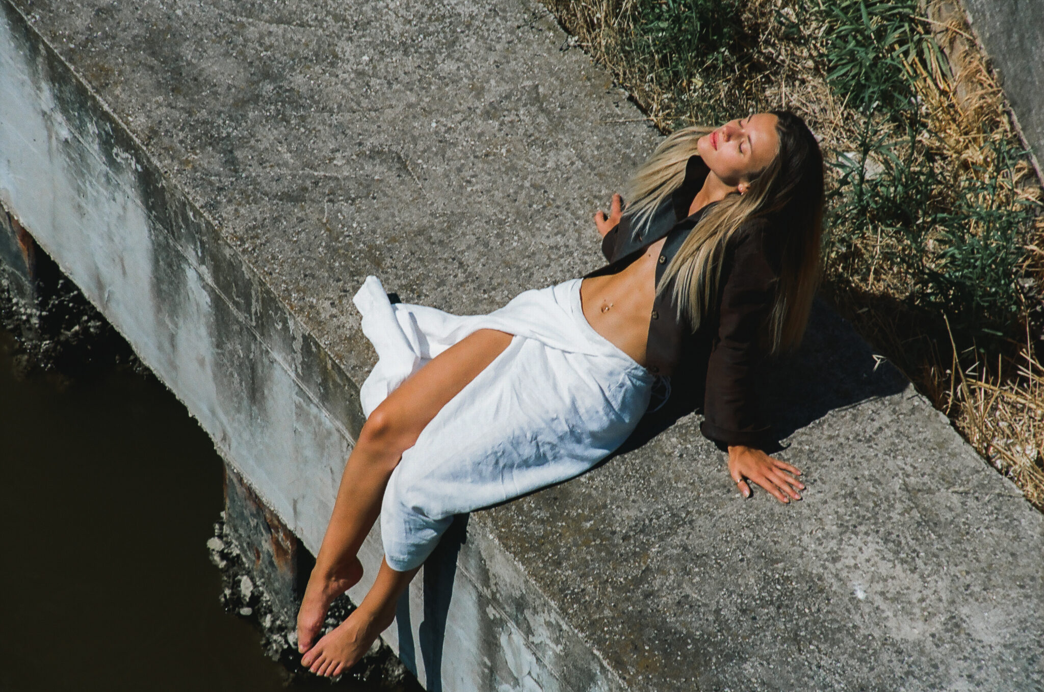 Modella bionda con gonna a portafoglio bianca, giacca di pelle marrone, prende il sole seduta su un argine, fotografia analogica