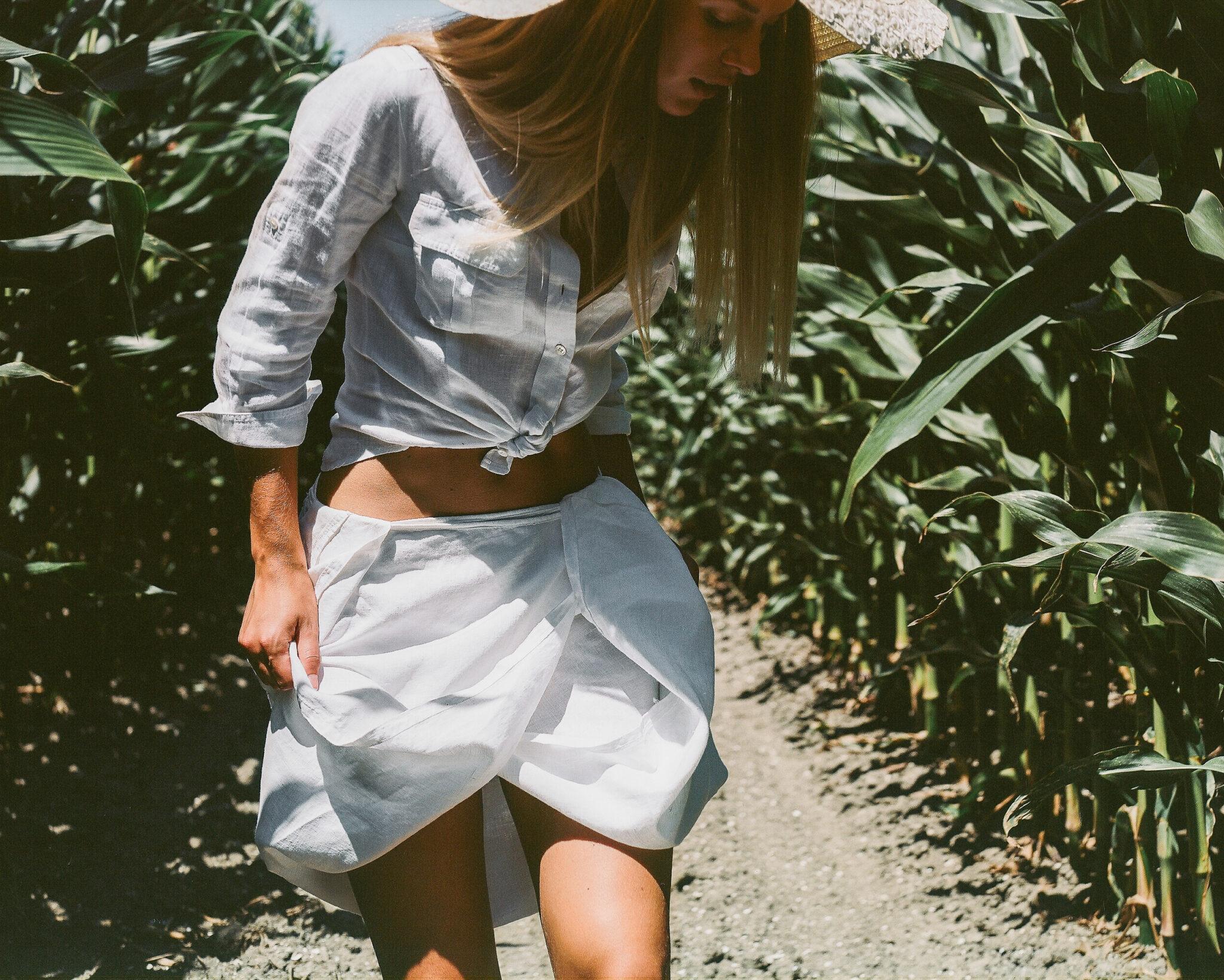 Modella con camicia bianca annodata e gonna raccolta in mezzo a un campo di pannocchie, fotografia analogica con Mamiya RZ67