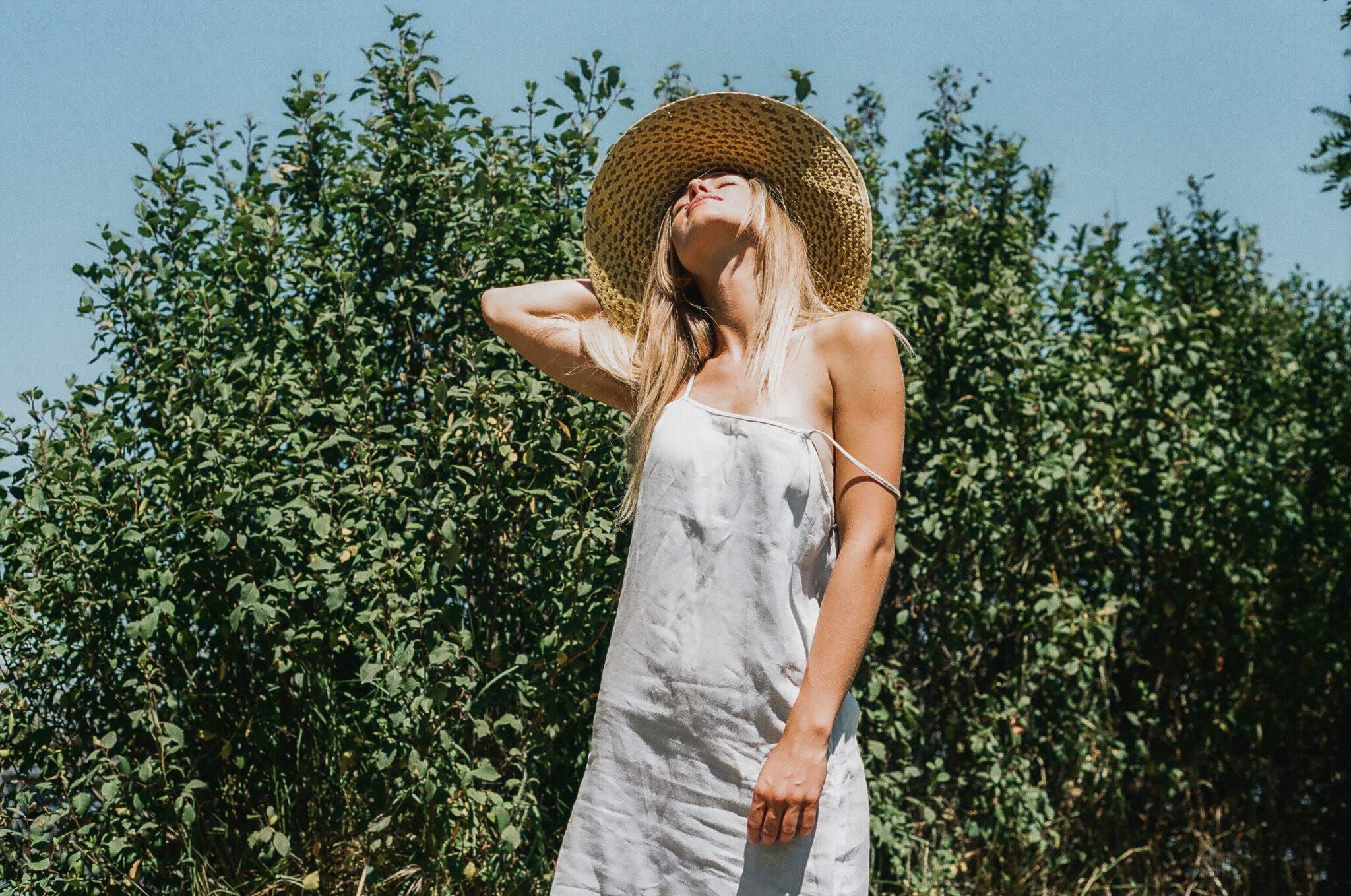 Modella bionda con vestito azzurro a spalline sottili e cappello di paglia di fronte ad alcuni alberi, fotografia analogica