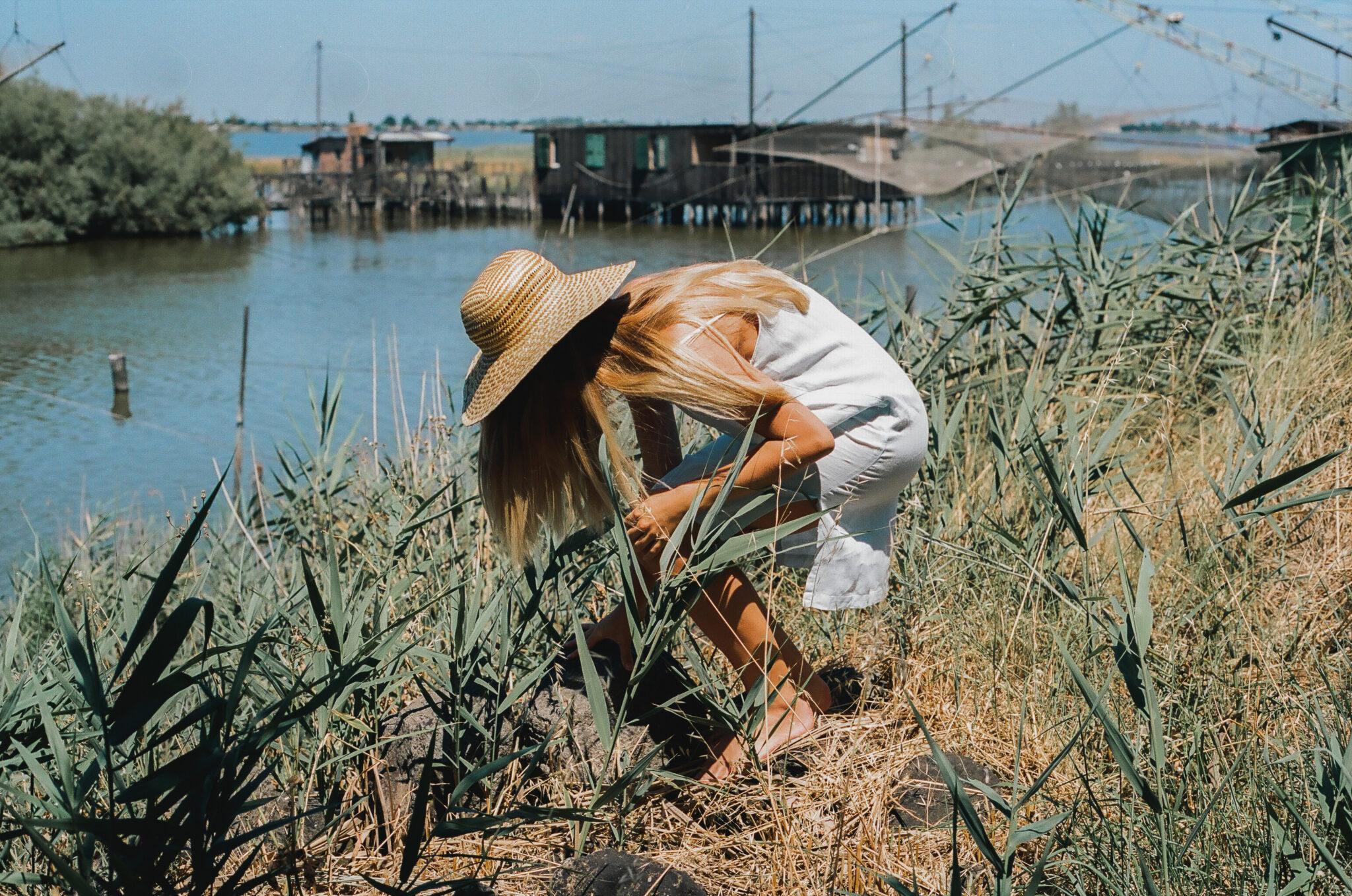 Modella con vestito azzurro e cappello di paglia, chinata in mezzo all'erba di fronte ad alcune palafitte, fotografia analogica