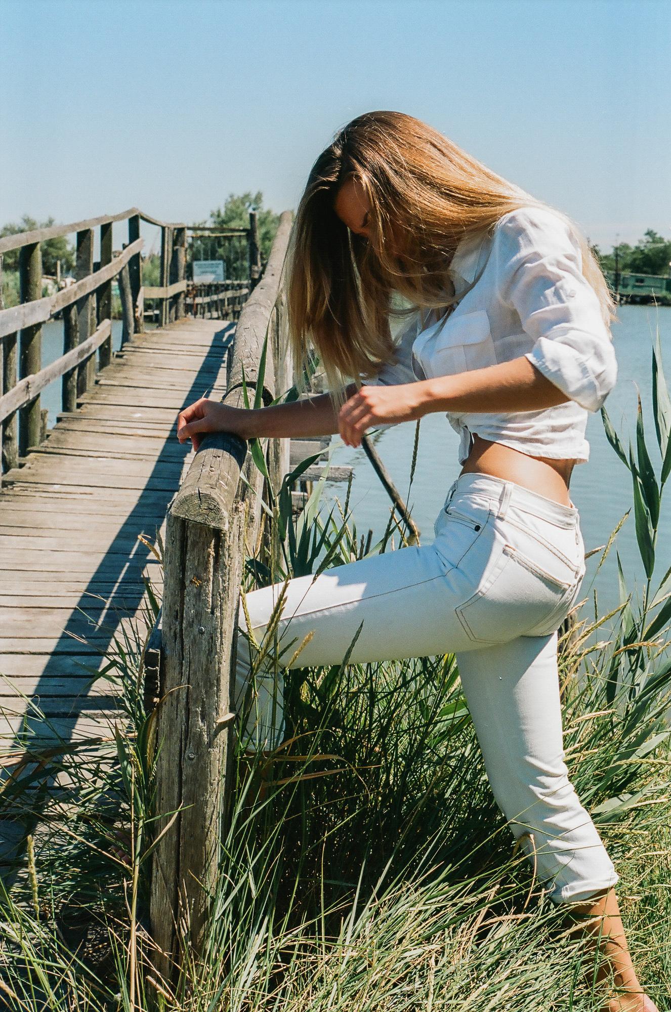 Modella con camicia bianca annodata e jeans bianchi su un ponte, fotografia analogica