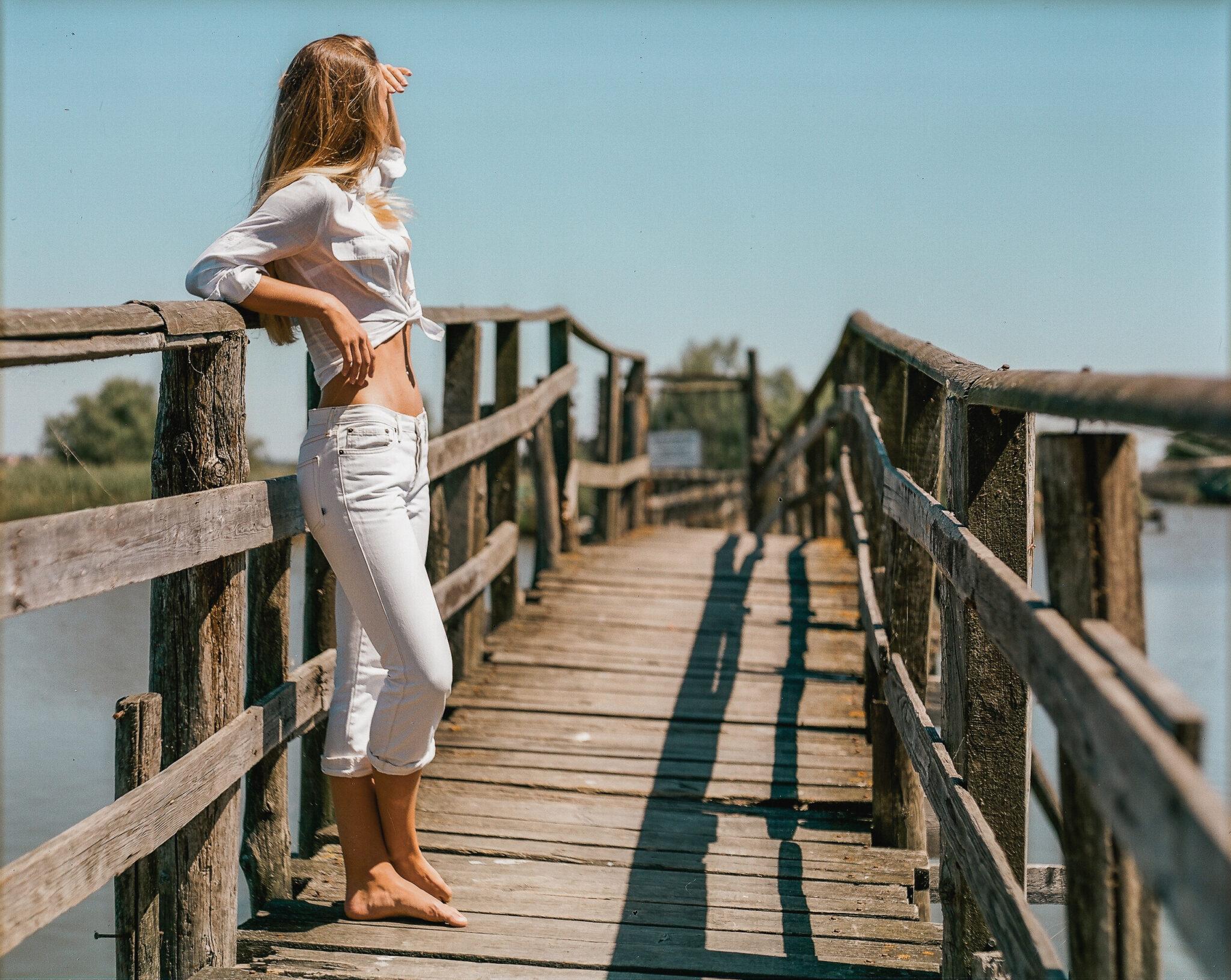 Modella con camicia bianca annodata e jeans bianchi su un ponte, guarda lontano, fotografia analogica