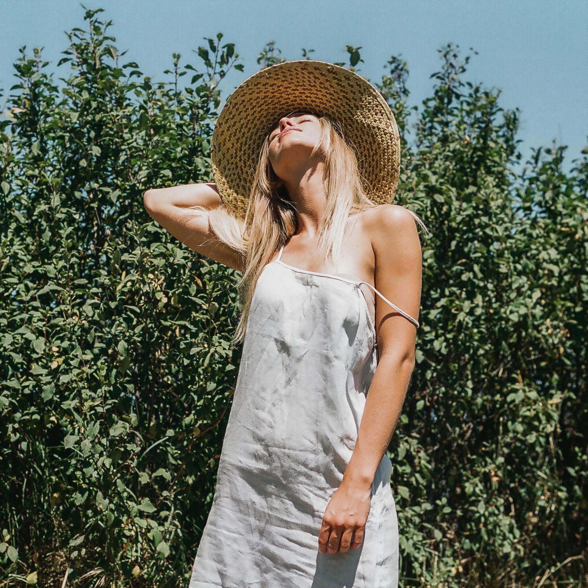 Modella bionda con vestito azzurro a spalline sottili e cappello di paglia di fronte ad alcuni alberi, fotografia di moda, analogica